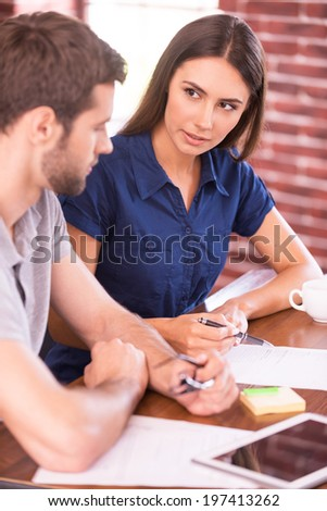 Discussing new business project. Side view of cheerful young man and woman sitting at the table and talking while man pointing digital tablet and smiling  - stock photo