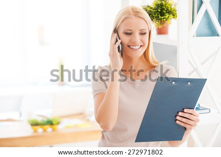 Discussing new project. Beautiful young woman leaning at the shelf in office and smiling while talking on the mobile phone and looking at clipboard  - stock photo