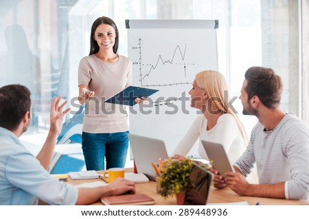 Discussing some business issues. Cheerful young woman standing near whiteboard and smiling while her colleagues sitting at the desk  - stock photo