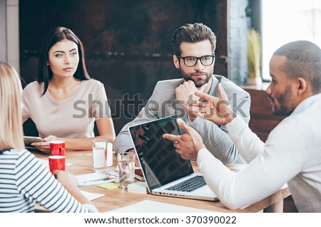 Discussing some business issues. Group of young people discussing something while sitting at the wooden table in the office - stock photo