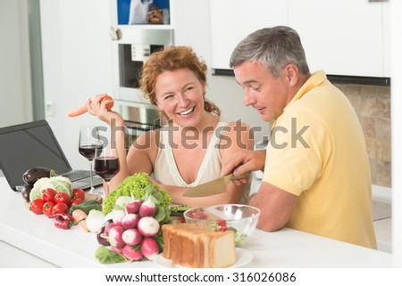 Discussion between mature man and woman in the kitchen. People drinking wine, having fun and discussing something. They both preparing vegetables salad.