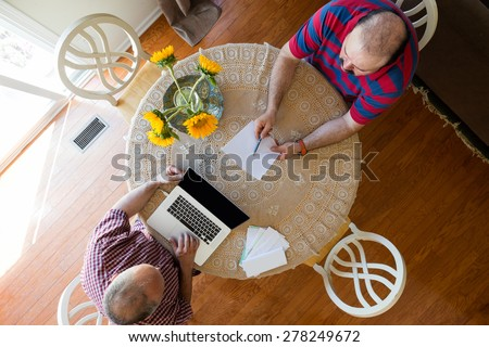 Discussion between two men seated at a round table decorated with yellow sunflowers using a laptop computer and paper documents, overhead view - stock photo