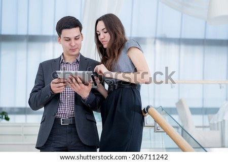 Discussion. businessman and businesswoman discussing things on the plate and stand on the stairs in the office in formal dress