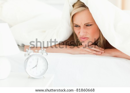 Disgruntled blonde woman waking up in her bedroom - stock photo