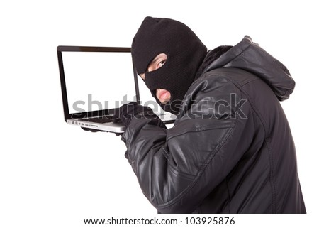 Disguised computer hacker with laptop - stock photo