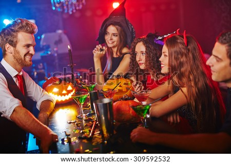 Disguised people drinking in club at Halloween night