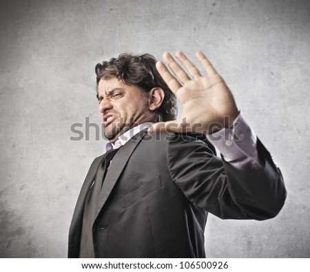 Disgusted businessman repulsing something with his hand