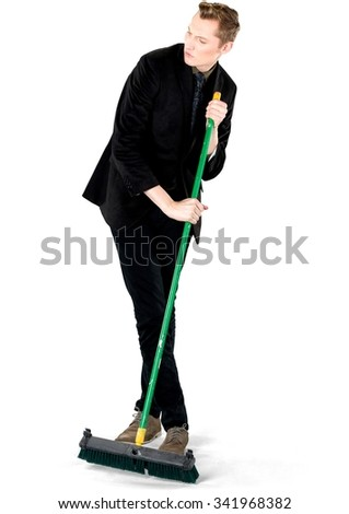 Disgusted Caucasian young man with short light blond hair in business formal outfit using broom - Isolated - stock photo