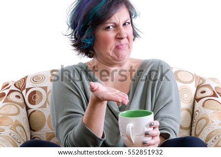 Disgusted woman in chair gesturing with hand to cup of tea, white background