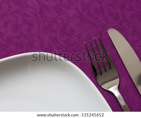 Dish, fork and knife in tablecloth, table arrangement background - stock photo