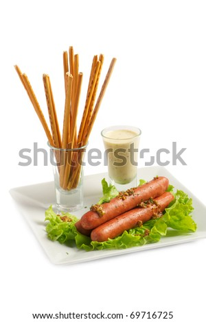 Dish from sausages a grill, sheet of salad, white sauce and grain sticks on a light plate on a white background - stock photo
