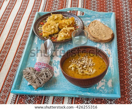 Dish Lithuanian, Polish, Belarusian cuisine rhombuses potato with fried onions, glass of vodka  and pumpkin soup on the tray - stock photo