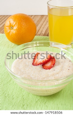 Dish of Amaranth and yogurt with and orange and a glass of orange juice - stock photo