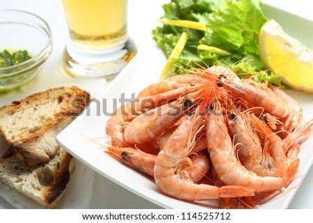 dish of fresh boiled prawns seasoned with sea salt, with lettuce, some bread and beer - stock photo