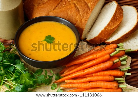 Dish of homemade Carrot and coriander soup in kitchen setting surrounded by ingredients and crusty bread - stock photo