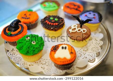 Dish of multicolor Halloween cupcakes - stock photo