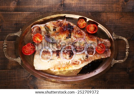 Dish of Pangasius fillet with spices and vegetables in metal tray on wooden table background - stock photo