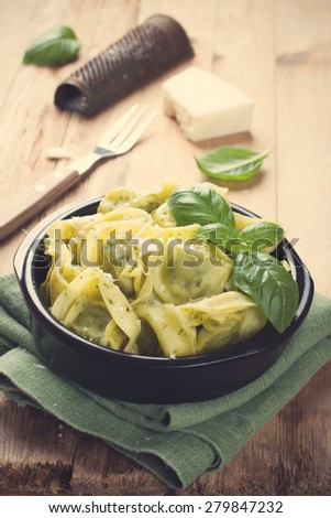 Dish of savory Italian tortellini pasta noodles filled with ricotta and spinach and fresh basil served with pecorino and fresh salad - rucola, cherry tomatoes and mozzarella. Selective focus. - stock photo