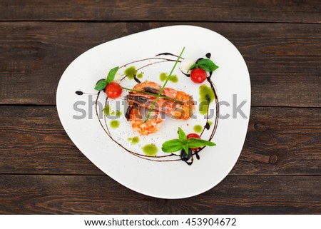 Dish of tasty grilled shrimps flat lay, copyspace. Top view on white triangle plate with fried prawns, decorated by chef at restaurant, on dark wooden background, flat lay - stock photo
