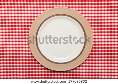 Dish on wooden table with red checked tablecloth
