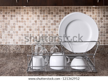 Dish rack with white plates and cups on kitchen countertop. - stock photo