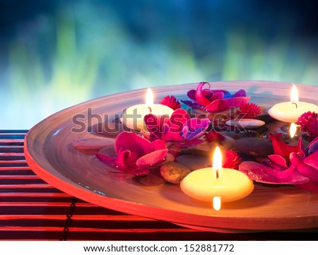 dish spa with floating candles, orchid, in garden - stock photo