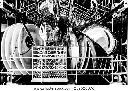 Dish washer full of clean dishes black and white - stock photo