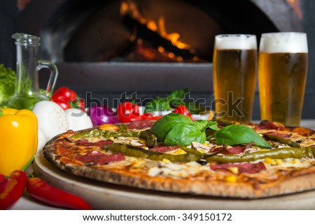 Dish which consist of delicious italian pizza made form a lot of fresh ingredients and glass of cold beer.  - stock photo