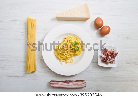 dish with carbonara's spaghetti and ingredients on white wood - stock photo