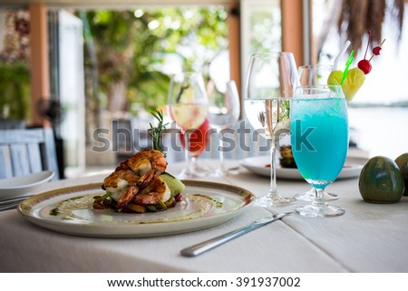 dish with cooked prawns with potato, blue cocktail with ice, beach sea view restaurant serving - stock photo