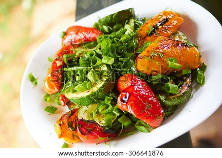 dish with grilled sweet peppers, zucchini, green onions and herbs in nature
