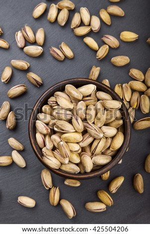 dish with pistachios on a slate, a top view - stock photo