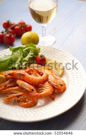 dish with shrimp salad and glass of wine - stock photo