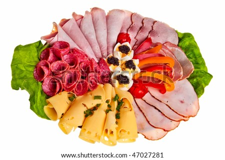 Dish with sliced ham, cheese and salami rolls, boiled eggs with black caviar and more. - stock photo