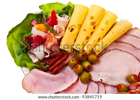 Dish with sliced smoked ham, salami rolls and cheese over white background. - stock photo