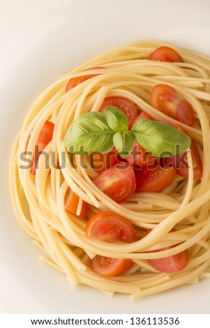dish with spaghetti tomatoes and basil