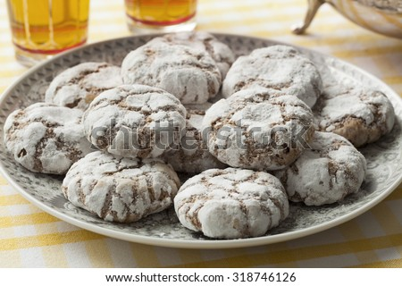 Dish with traditional Moroccan Ghribas cookies with tea - stock photo