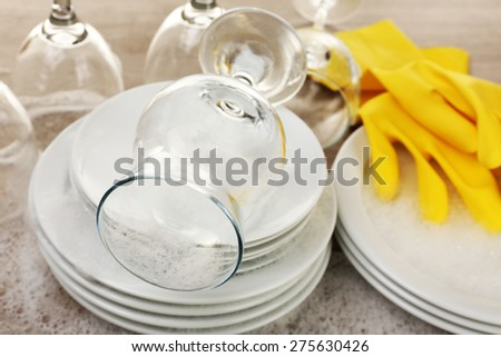 Dishes in foam with gloves on table close up - stock photo