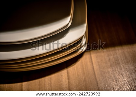 Dishes in light and shadow on wooden floor - stock photo