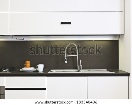 dishes on the worktop near to the sink and faucet in a modern kitchen  - stock photo
