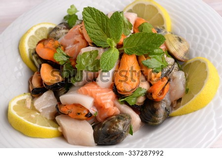 Dishes with seafood, shellfish and fish on white and colored - stock photo