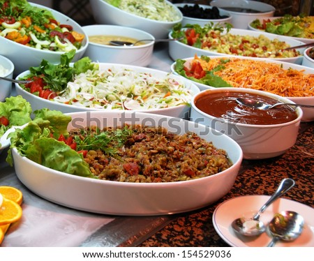 dishes with various salads in buffet restaurant - stock photo