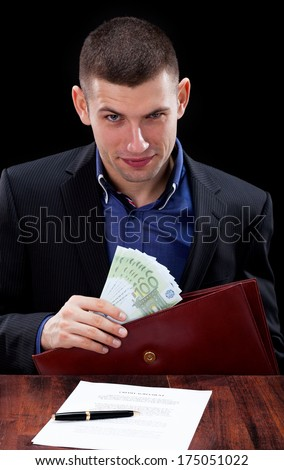 Dishonest businessman taking a bribe for signing unfair contract - stock photo