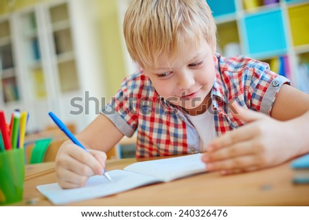 Dishonest schoolboy looking at crib on his palm while writing test - stock photo