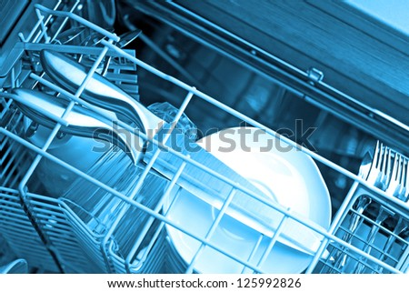 Dishwasher after cleaning process, blue tone - stock photo