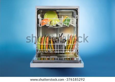 Dishwasher full of utensils isolated against blue background - stock photo