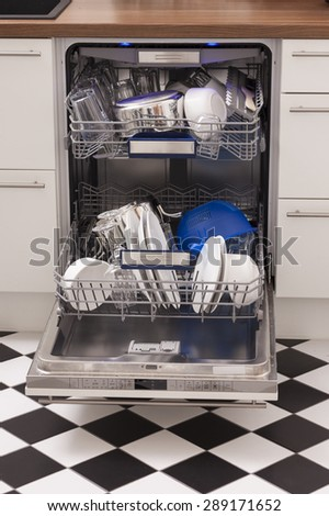Dishwasher loades in a kitchen with clean dishes and blue light - stock photo