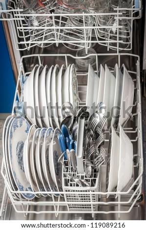 Dishwasher machine opened after finished job. - stock photo