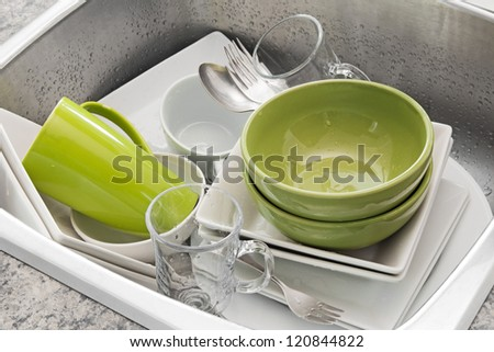Dishwashing. Bright dishes in the kitchen sink. - stock photo