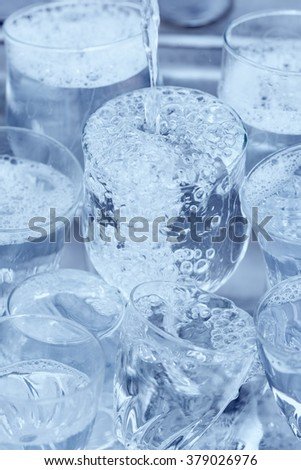 Dishwashing - Glassware under a water jet in the kitchen sink - stock photo